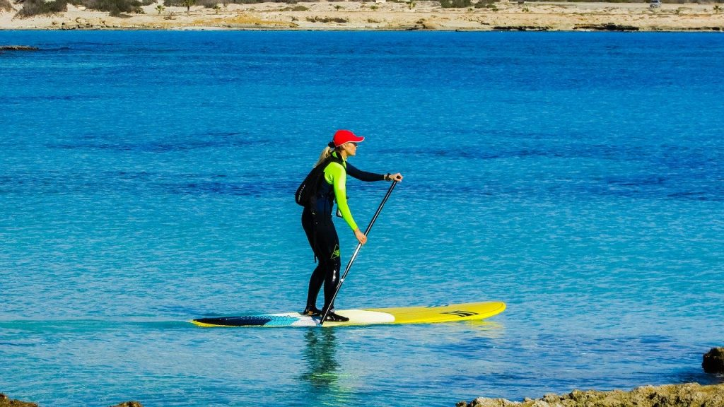 woman paddleboarding on ocean in wetsuit