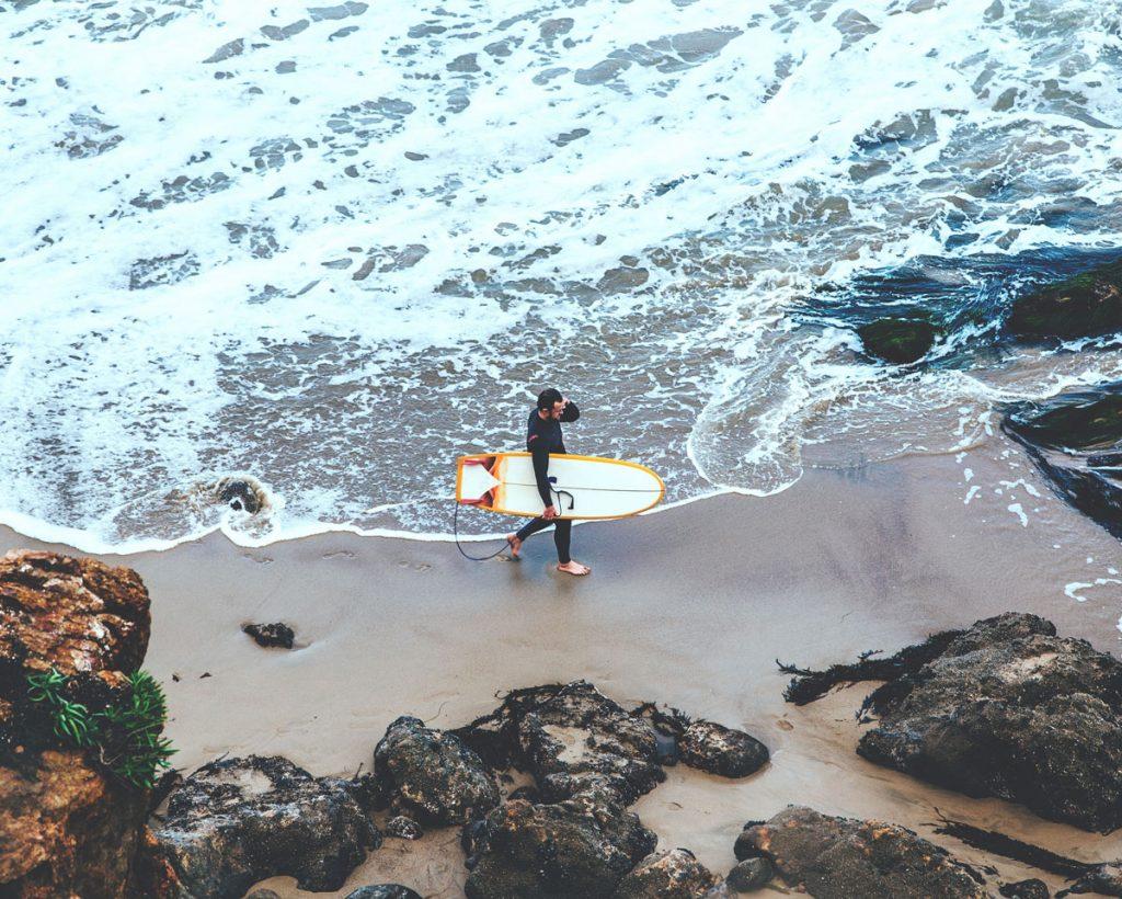 Man-Walking-Beach-Board
