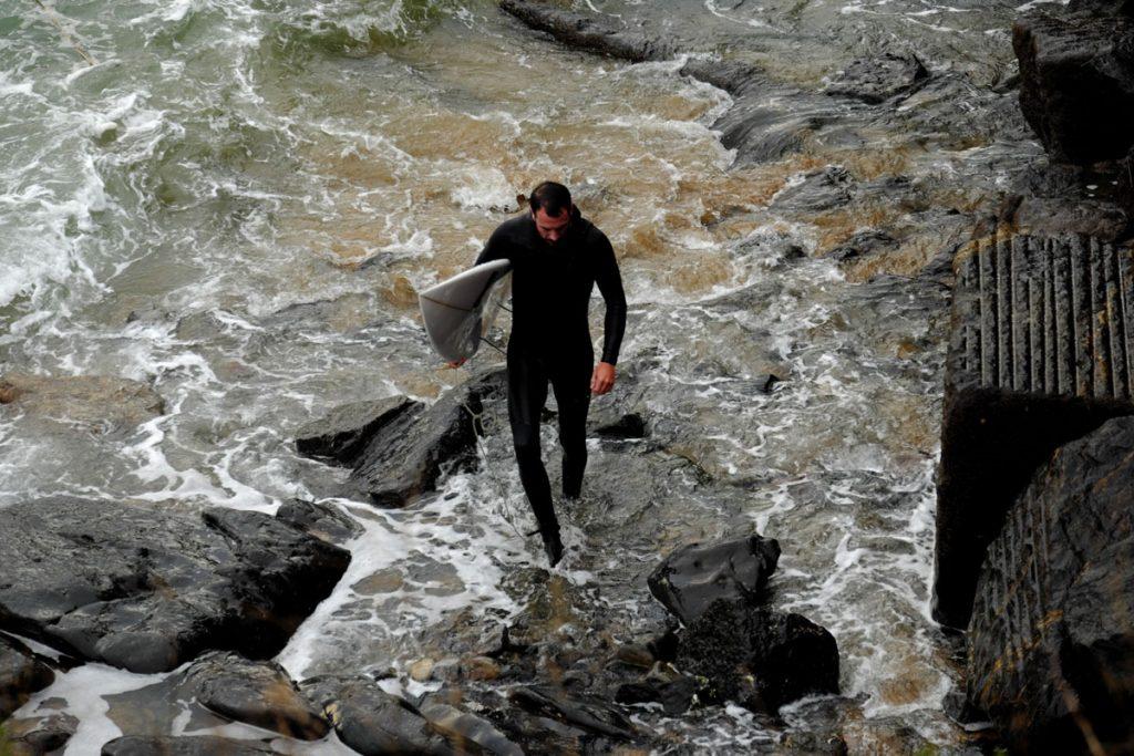 Man-Wetsuit-Board-Rocks