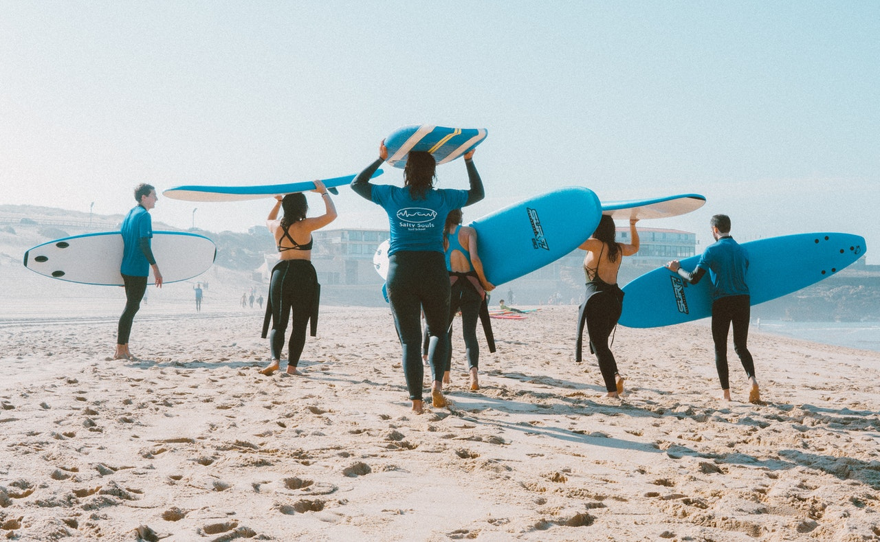 group-people-surfboards-wetsuits