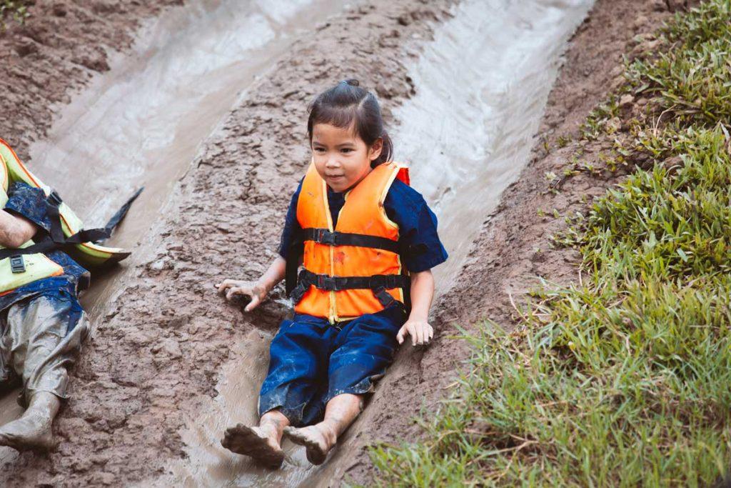 Niña con chaleco-salvavidas-infantil por un tobogán de barro