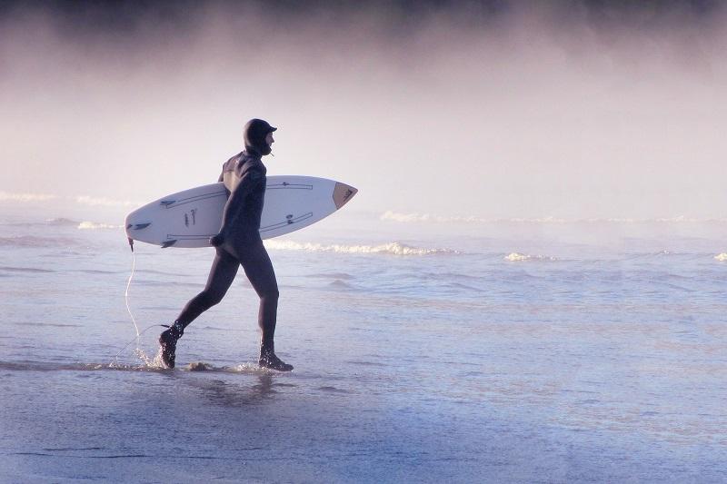 Surfero con tabla de surf llevando una capucha de neopreno