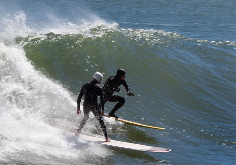 Surferos llevando trajes con capucha de neopreno